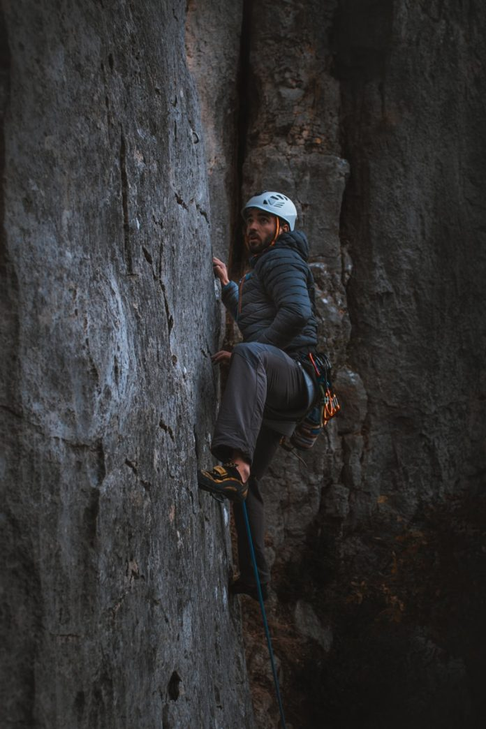 man in black jacket and white cap climbing on gray rock