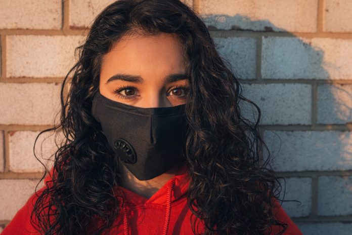 woman in red shirt wearing black mask